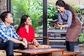 Indian waitress taking orders of two customers in cafe or restaurant poster