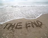 The End Text Written On The Sand And The Wave That Is Deleting T poster