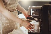 Woman Making Fresh Espresso In Coffee Maker. Coffee Machine Makes Coffee. poster