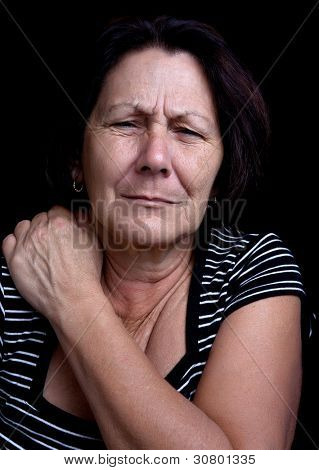 Portrait of a senior lady suffering from shoulder pain on a black background
