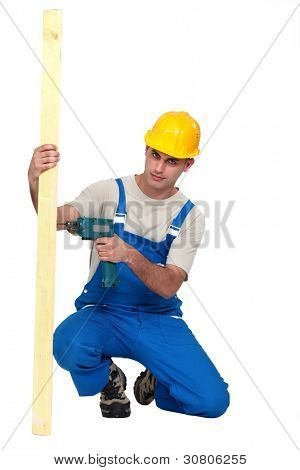 Man drilling hole in to plank of wood