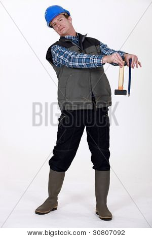 craftsman holding a hammer and a wedge and looking disgusted