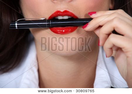 Woman with pen in mouth