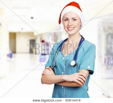 Smiling female medical doctor wearing red hat in a hall of a hospital. Christmas time concept.