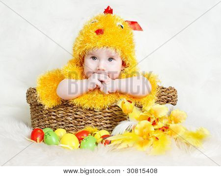 Baby In Easter Basket With Eggs In Chicken Costume.