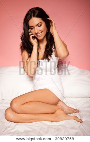Beautiful brunette woman relaxing curled up on her bed talking on her mobile phone.