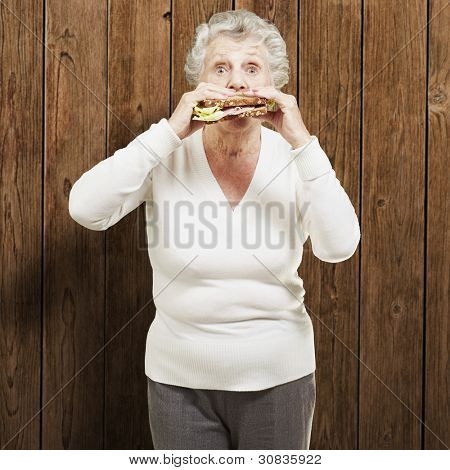 senior woman eating a healthy sandwich against a wooden background