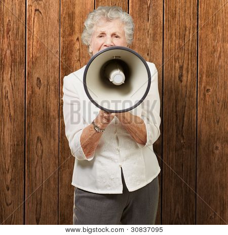 portrait of senior woman screaming with megaphone against a wooden wall