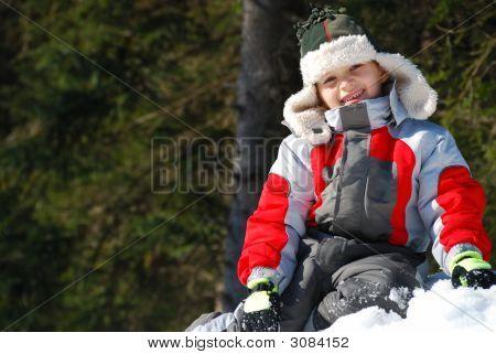 Happy Boy On Snowbank