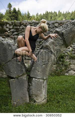 Blonde girl on a stone monument