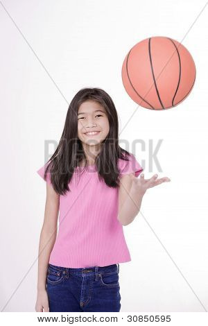 Ten Year Old Asian Girl tossing Basketball, Isolated On White