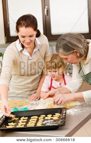 Happy little girl rolling out dough with mum and grandmother