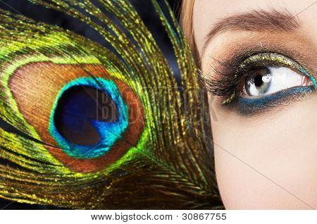 Woman eye with colorful makeup and peacock feather