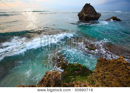 Rocky coast of Indian ocean at sunset light. Bali island