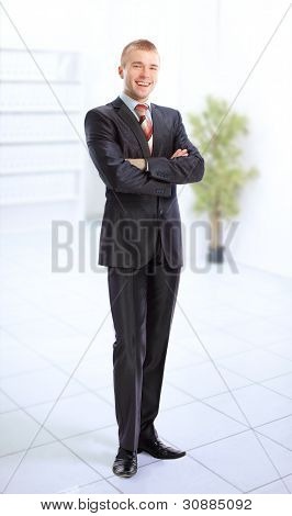 Young smiling business man standing in a light and mordern business hall.