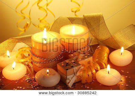 schöne Kerzen, Geschenke und Dekorationen auf Holztisch auf gelbem Grund