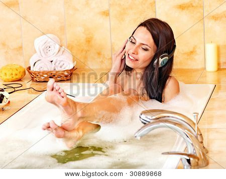Young woman listening to music in bubble  bath.