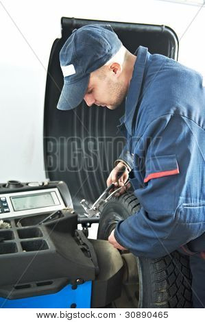 mechanic repairman at car tyre fitting and balancing adjustment using special equipment