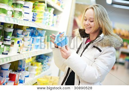 woman choosing bio food produces in dairy shopping mall