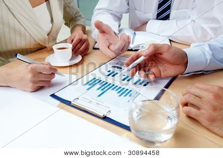 Close-up of human hands during discussion of business documents at meeting
