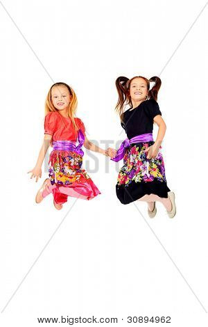 Portrait of two happy girls sisters jumping at studio. Isolated over white.