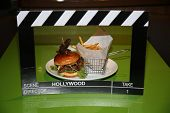Bacon and Cheese Hamburger and French Fries on a green table with a Hollywood Movie Placard or Click poster