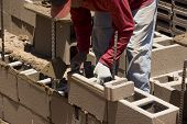 picture of cinder block  - Migrant worker building cinder block wall in desert setting - JPG