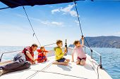 Two Little Kid Boys, Father And Toddler Girl Enjoying Sailing Boat Trip. Family Vacations On Ocean O poster