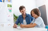 Father and son doing homework together at home poster