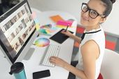 High angle view of Asian female graphic designer using graphic tablet at desk in a modern office poster
