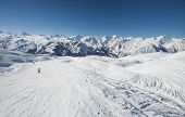 Panoramic Landscape Valley View With Skiers Going Down A Ski Slope Piste In Winter Alpine Mountain R poster