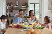 Front view of happy Caucasian family having food and champagne on dining table at home poster