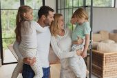 Front view of happy Caucasian parents holding their children at home poster