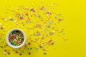Sprinkles On Bright Yellow Background With Little White Bowl With Various Type Of Coloured Sprinkles poster