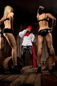 stock photo of promiscuous  - Pirate  with pair Sexy passionate girls against wooden background - JPG