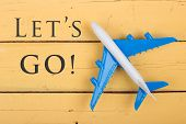 Model Of Airplane And Text Lets Go! On Yellow Wooden Background poster