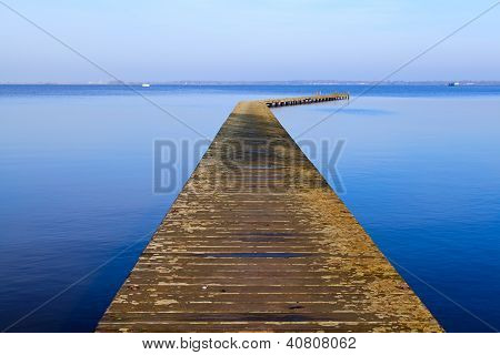 Long Wooden Pier On Blue Sea