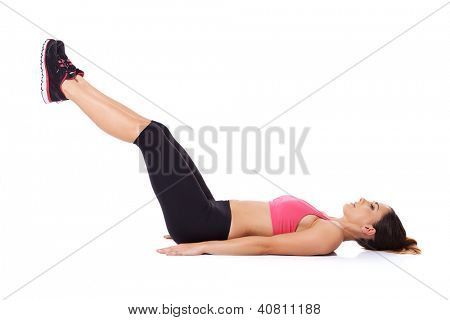 Woman doing leg lifts to strengthen her abdominal muscles while lying on the floor working out, studio portrait over white