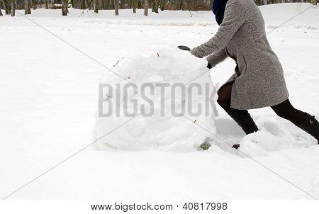 woman grey coat push big snow roll winter meadow