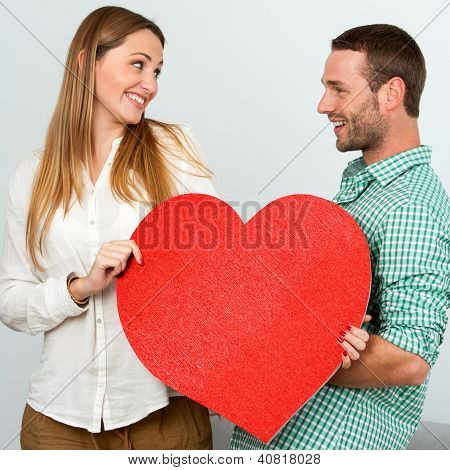 Cute Couple Holding Big Red Heart Sign.