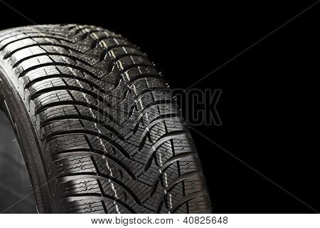 Part of new winter automobile car tyre on black backgroung