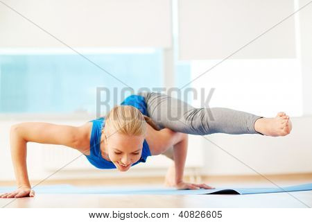 Portrait of young woman doing physical exercise in gym
