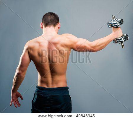 Vista posterior de un joven culturista masculino haciendo peso pesado ejercicio con pesas contra backg gris