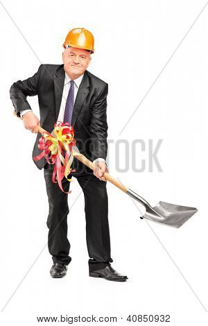Full length portrait of a businessman wearing helmet and holding a shovel with ribbon on it isolated on white background