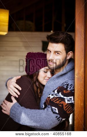 Young couple in a cabin in romantic scape in winter, She is leaning on his chest