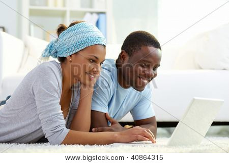 Relaxed couple using a laptop to surf the internet