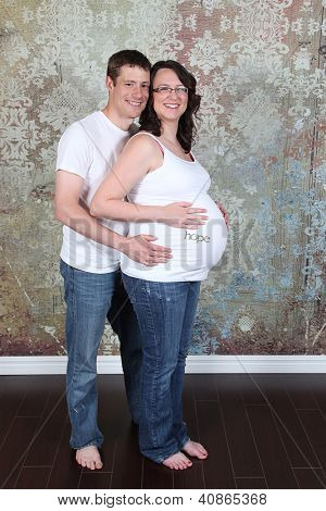 Maternity photos of a woman with brink wall as a background - 8 months pregnant
