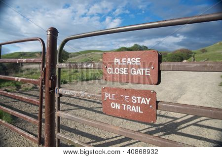 Sign reminds visitors to stay on the trail and to close the gate