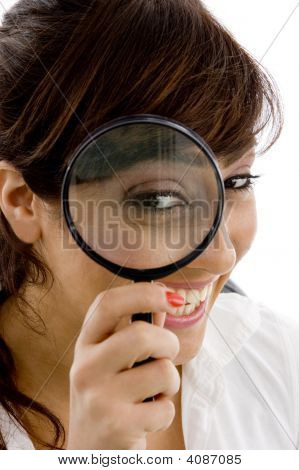 Front View Of Smiling Female Holding Magnifier Close To Eye