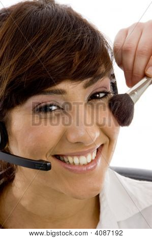 Close Up Of Smiling Female Customer Care Executive Applying Blusher